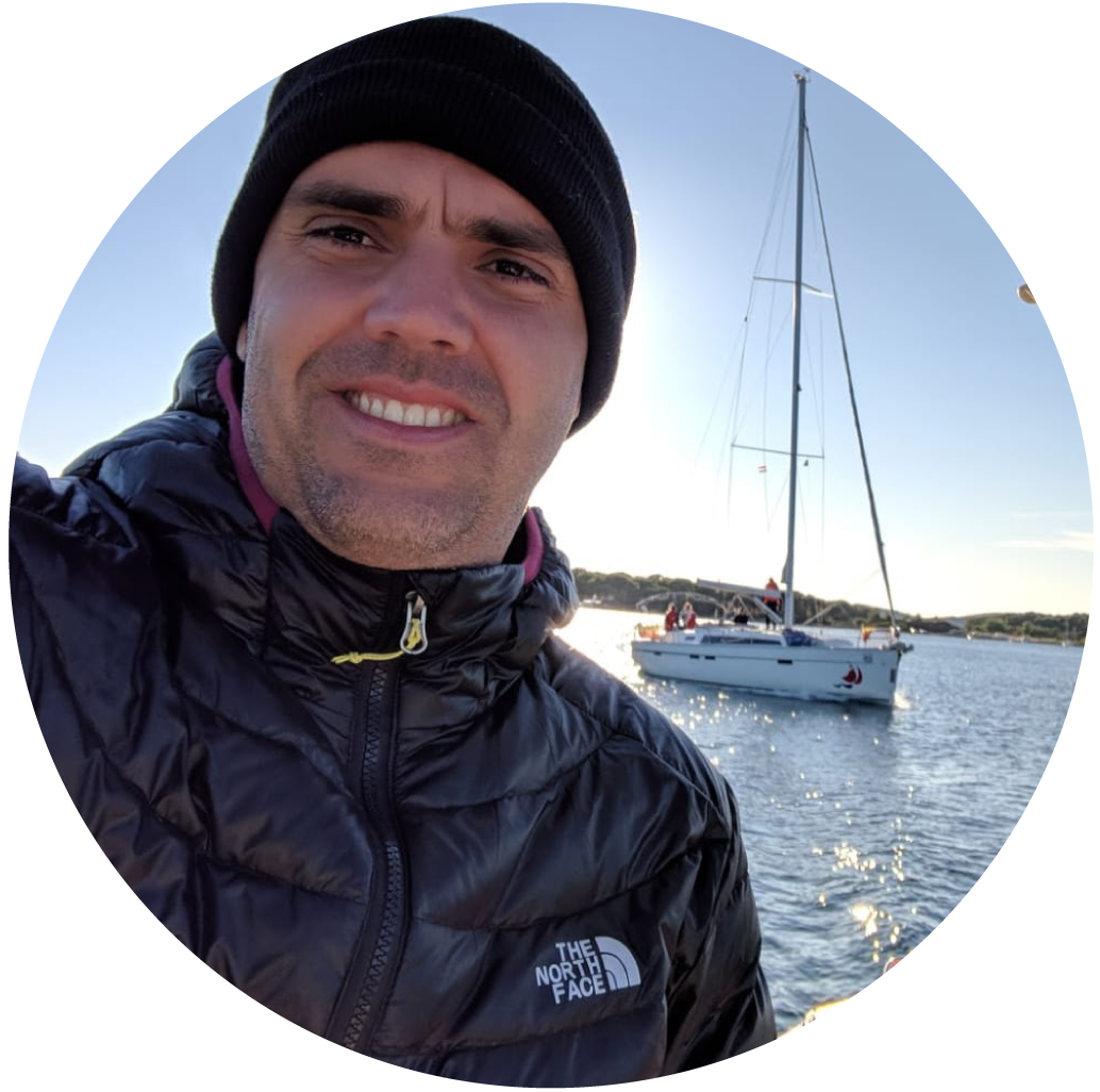 Photo of Alberto Silveira, a 40-something white man wearing a woolen cap and black winter jacket. In the background, a small boat with sails down floats in the harbor